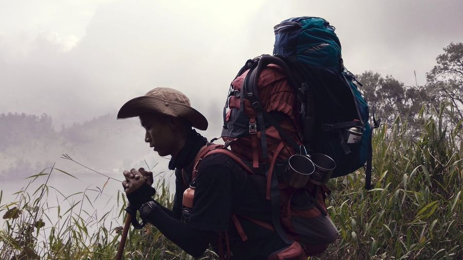 Side View Of Man Carrying Heavy Backpacks On Land