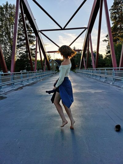 Rear View Of Girl Dancing On Bridge