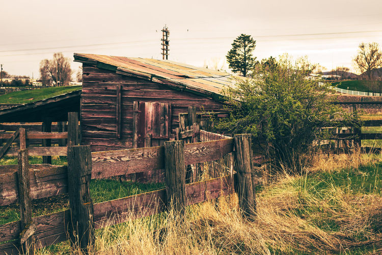 Old wooden house on field against sky