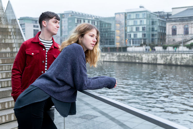 Couple Standing By River In City