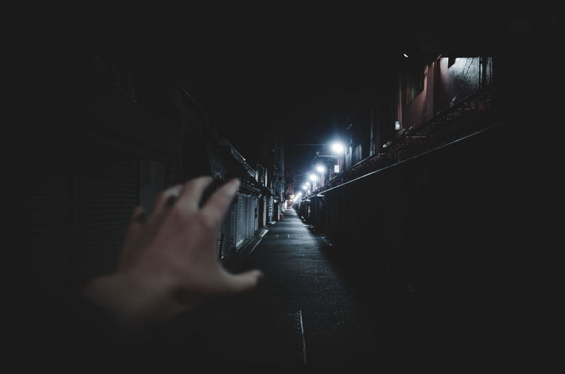 Cropped Hand Of Woman Gesturing At Alley During Night