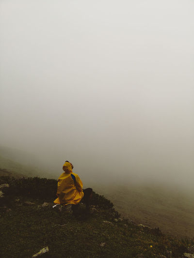 Person Sitting On Rock Against Sky During Foggy Weather