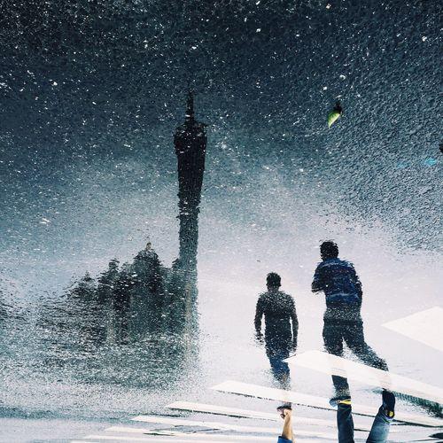 People reflecting on puddle