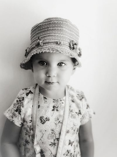 Portrait of cute girl wearing hat against white background