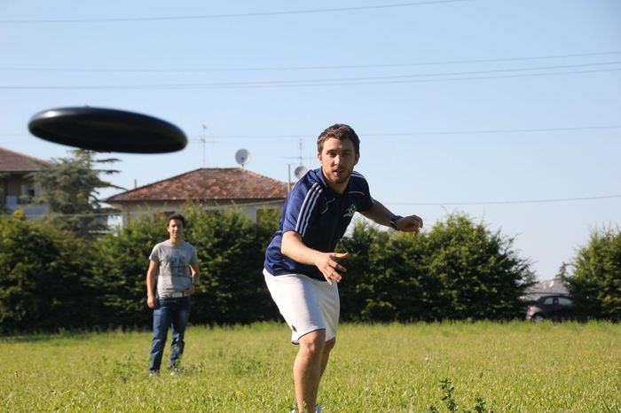 Lifestyles Fresbee Ultimate Frisbee Grass Casual Clothing Togetherness Mid Adult Men Two People Walking Full Length Standing Day Father Outdoors Fun Carrying Men Leisure Activity Sky Happiness Real People Smiling Tree Sport Smile