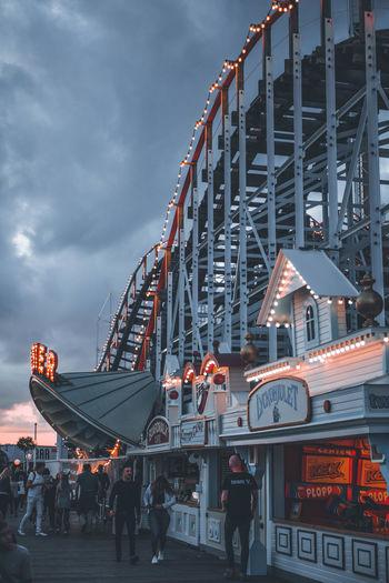 People at amusement park against sky