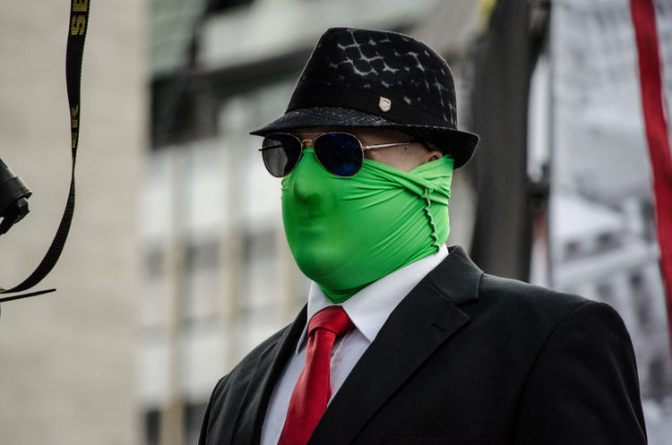 Anonymous Black Suit Casual Clothing Close-up Colorful Day Demonstration Focus On Foreground Green Mask Hat Hat Lifestyles Mask Masked Maskedportraits Multi Colored Outdoors Protester Selective Focus Warm Clothing Wearing