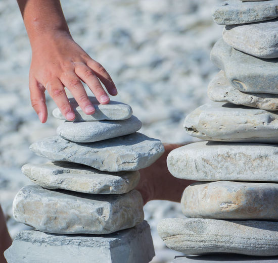 the towers of pebble stones on the beach, games on the beach Stack Focus On Foreground Human Hand Balance Human Body Part Solid Hand Real People Day Stone - Object One Person Body Part Close-up Rock Leisure Activity Nature Human Leg Lifestyles Stone Pebble Finger