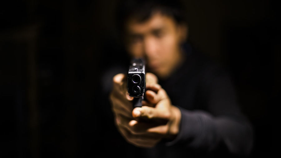 Close-up of man holding gun in darkroom