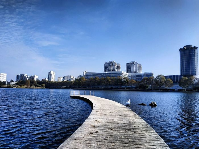 Jetty over river in city against blue sky