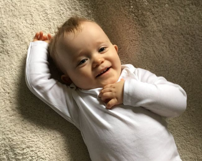 Portrait of smiling baby boy relaxing on rug at home