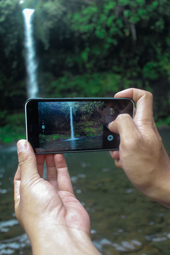 Cropped hands of person photographing waterfall with mobile phone in forest