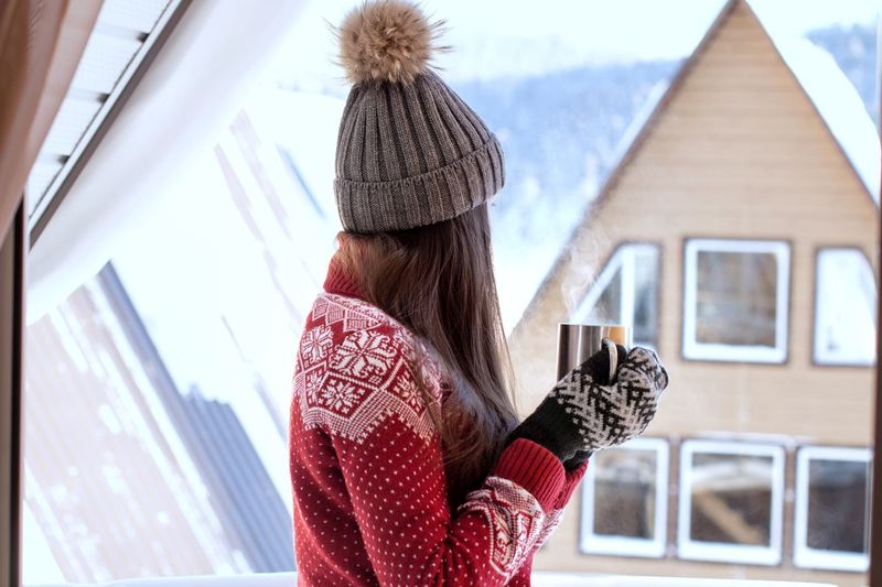 Young woman in red sweater holding hot drink in winter Winter Activities Lifestyle Morning Village View Hot Tea Cozy Mittens Hot Drink Winter Sweaterweather Morning In The Mountains Steam Warming Snowy Mug Hot Coffee Winter Warm Clothing Cold Temperature One Person Women Day Lifestyles Outdoors Snow Leisure Activity