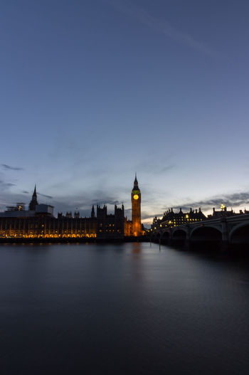 Illuminated big bien by thames river against sky