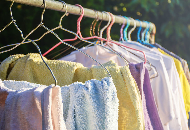Colorful towels and clothes hanged on rail drying in afternoon sunlight. Clean Clothes Housework Hygiene Laundry Shirts Sun Drying Sunlight Washing Clothes Cloth Cleaning Cloth Rail Clothesline Clothing Colorful Day Drying Clothes Hanging Multi Colored Outdoor Towels Variation Yard