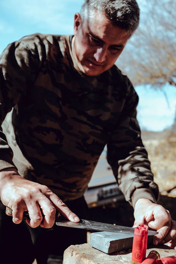 Man sharpening knife on rock