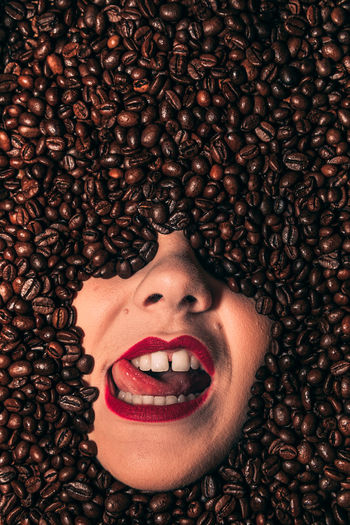 Face of a young, passionate female covered with coffee beans.