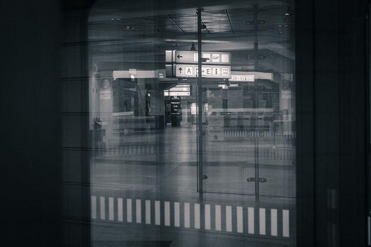 Text on railroad station platform seen through train window