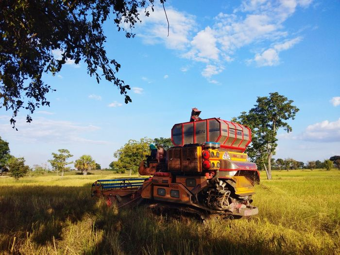Abandoned train on field against sky