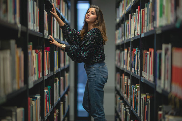 Side view of young woman looking at books in library