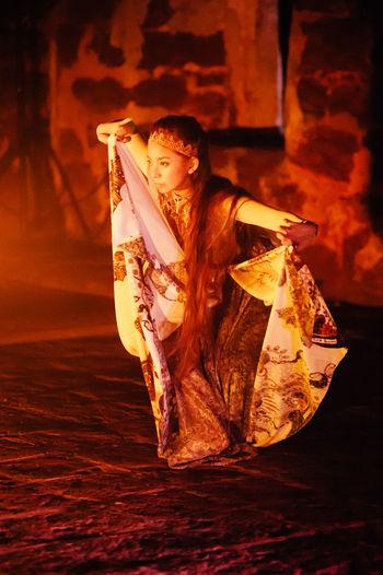Woman wearing costume while dancing in darkroom