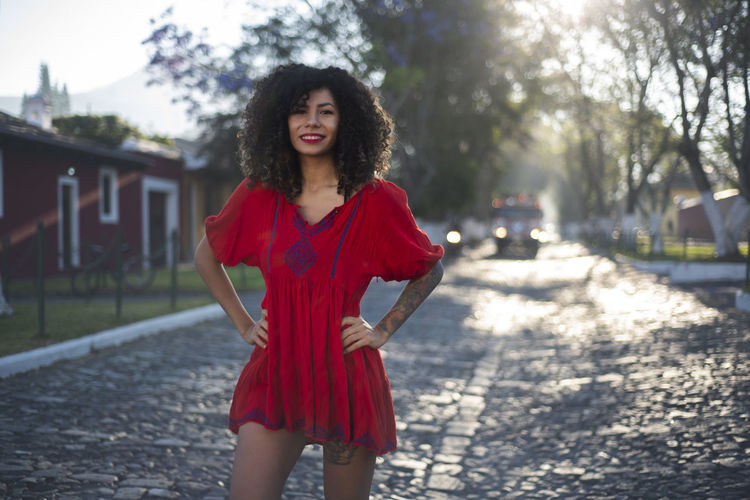 Red Dress Beautiful Woman Beauty Curly Hair Day Fashion Focus On Foreground Front View Hair Hairstyle Looking At Camera One Person Outdoors Portrait Real People Red Standing Three Quarter Length Tree Women Young Adult Young Women