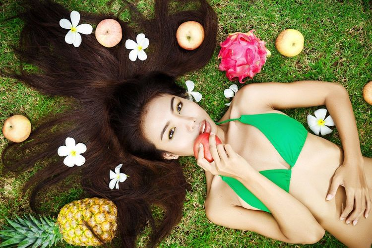 Portrait of young woman lying on grassy field surrounded with fruits and flowers