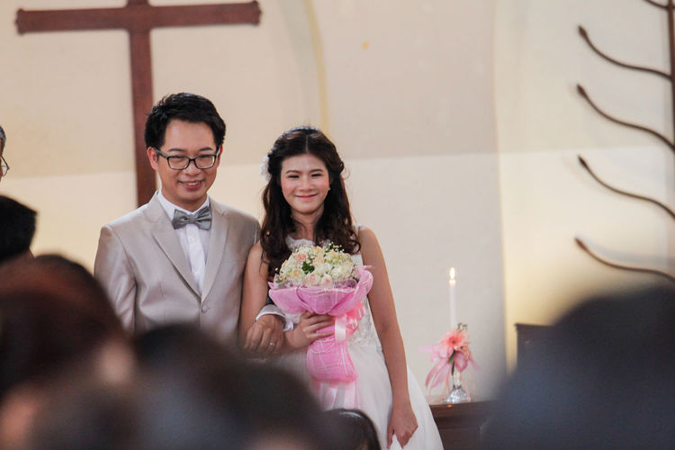 Bride And Bridegroom Standing At Church During Wedding Ceremony