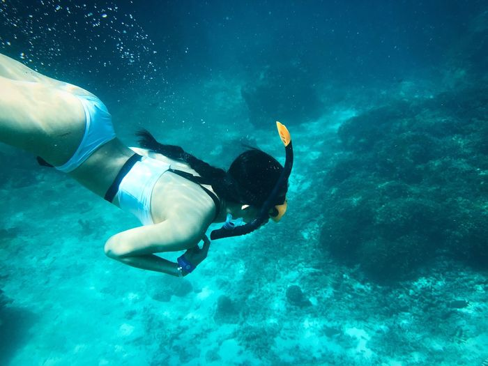 High angle view of woman swimming underwater in sea
