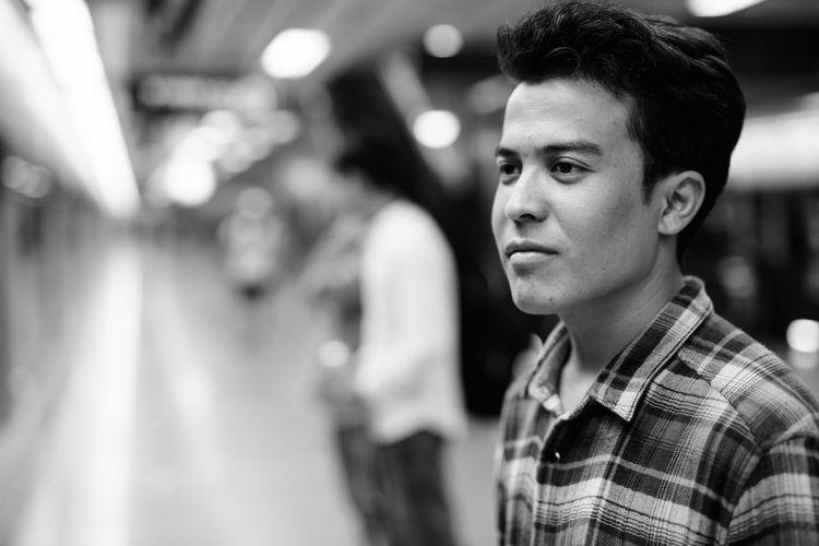 Young man looking away at subway station