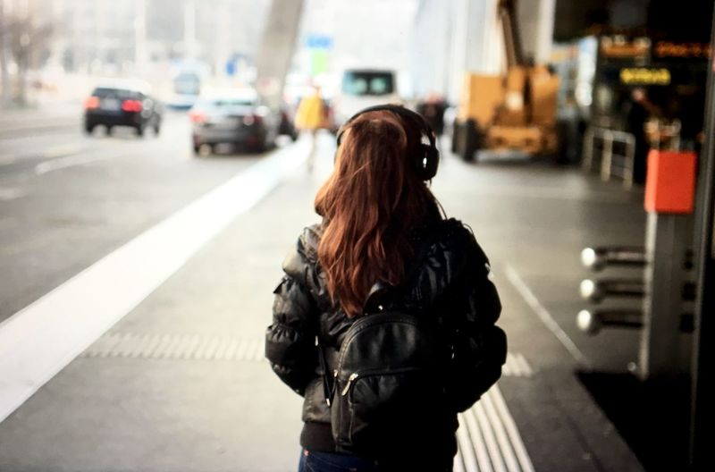 Rear View Of Woman Using Headphones Outside Airport