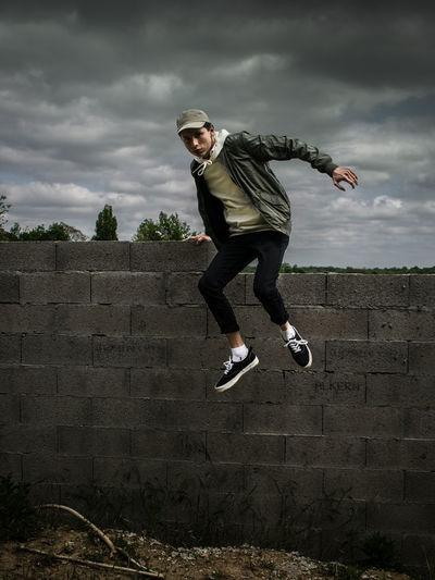 Full length of man jumping from wall against cloudy sky
