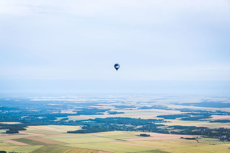 Adventure Air Vehicle Balloon Beauty In Nature Day Environment Field Flying Hot Air Balloon Land Landscape Mid-air Nature No People Outdoors Parachute Scenics - Nature Sky Tranquil Scene Tranquility Transportation