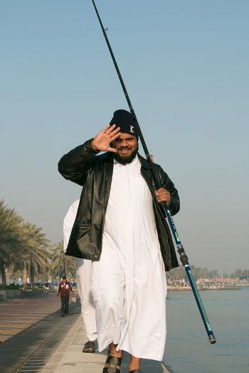 Portrait of happy man with fishing rod walking on promenade against sky