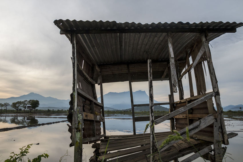 Kampung Sangkir, Kota Belud, Sabah- 22 January 2018: View of Mount Kinabalu within frame of old hut that waiting time to collapse. Borneo Kota Belud Reflection Architecture Background Beauty In Nature Built Structure Cloud - Sky Day Kinabalu Mountain Mountain Range Nature No People Old Outdoors Paddy Field Sabah Sabah Borneo Scenics Sea Seasoned Sky Water Wood - Material