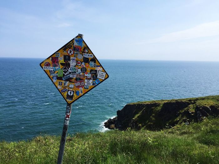 Stickers Stuck On Information Sign At Cliff Walk Against Sea