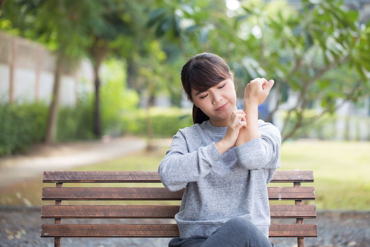 Young woman scratching hand while sitting on bench at park