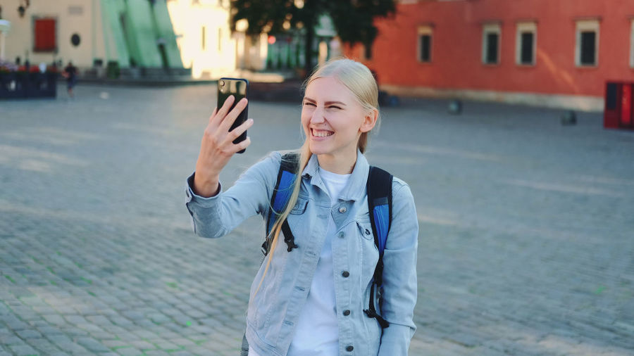 Smiling young man using mobile phone standing in city