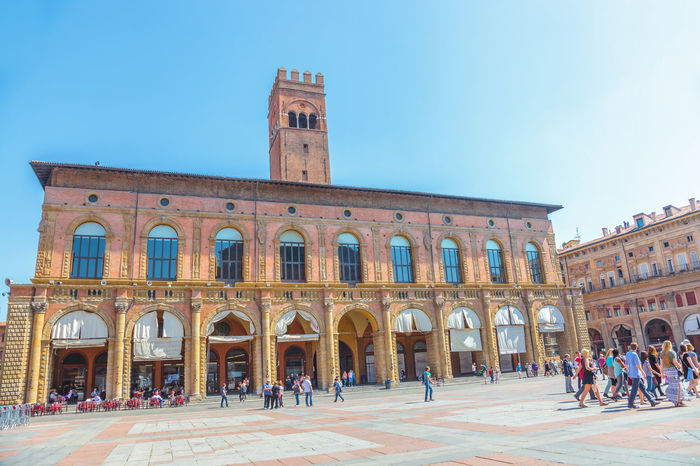 Bologna, Italy - May 28, 2016: Palazzo Re Enzo, historical landmark palace and heart of economic and social activities of the city with many people and the main square called Piazza Maggiore. People walking in via Rizzoli, restricted traffic zone, closed to traffic during the day on Saturday. The Two Towers, icons of Bologna, on background. Tourist train at side of Palazzo dei Banchi in Piazza Maggiore. San Luca Espress is the tourist line which connects the historic center with the Basilica of San Luca. Bologna Bologna, Italy Cathedral Church City Piazza Maggiore San Luca Tourist Ancient Civilization Arch Architecture Asinelli Asinelli Tower  Building Exterior Built Structure City Clear Sky Crowd Day Group Of People History Italian Italy Large Group Of People Men Nature Outdoors People Real People San Petronio Sky Street Streetphotography The Past Tourism Town Train Travel Travel Destinations Visit Women