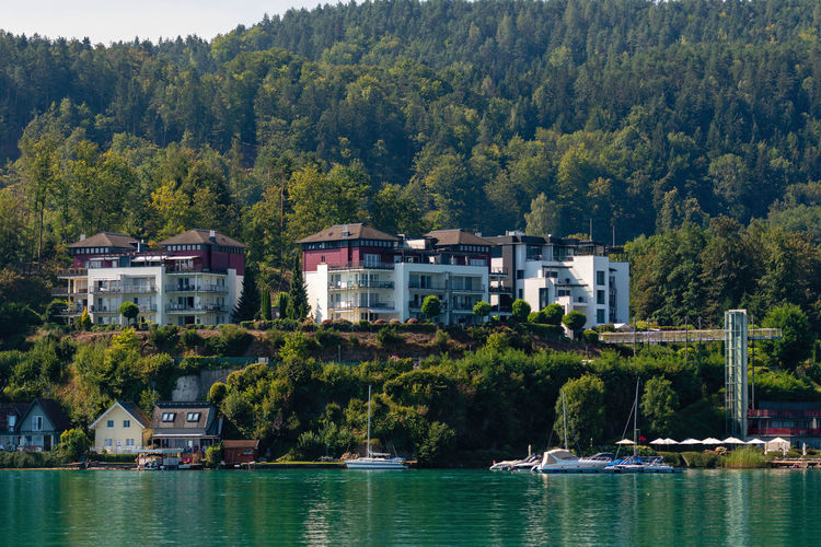 WORTHERSEE, AUSTRIA - AUGUST 08, 2018: Great scenery from the boat to the shore line of the lake, beautiful buildings, mountains, forests, highways. Tourists who enjoy a variety of water recreation types. Nature Day Outdoors Austria Carinthia Carinthian Lakes Tourist Tourists Lake Wörthersee Recreation  Leisure Landscape Water Sea Boats Motorboat Speedboats Summer People Holidays Fun Travel Beach Resort Lifestyle Sunny Rest Joy Waves Europe Alps Alpine Alpine Lake Tree Architecture Plant Built Structure Building Exterior Building Nautical Vessel Transportation Waterfront Residential District No People Mode Of Transportation House Forest Land