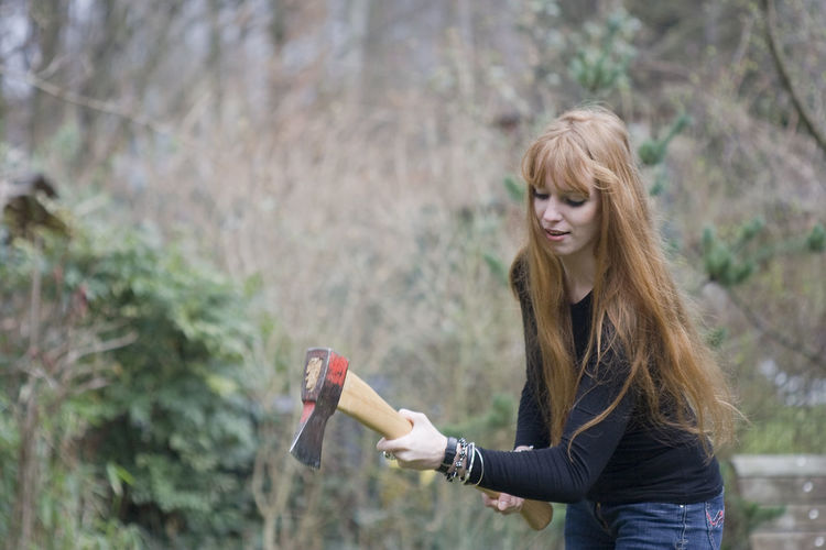 Woman cutting firewood with axe