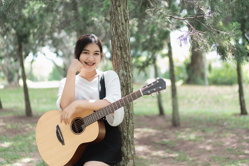 Portrait of young woman holding guitar standing by tree