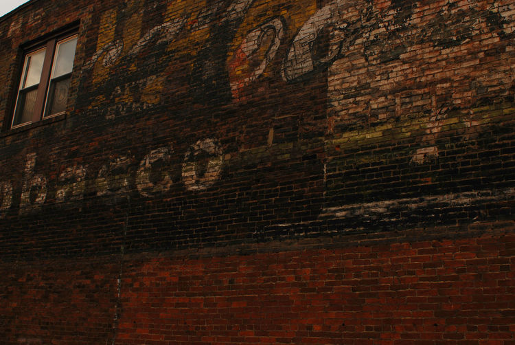 brick alley wall with remainders of text from vintage painted ads Ads Architecture Backgrounds Brick Brick Building Brick Wall Brick Wall Building Built Structure Close-up Day Deterioration Full Frame No People Old Town Old-fashioned Outdoors Text Vintage Window