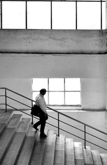 Rear view of man walking on railing against wall