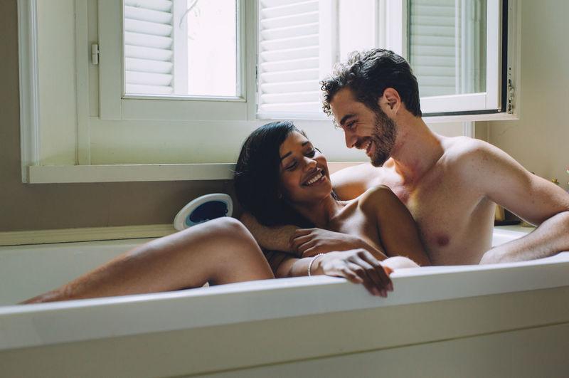 Happy couple sitting in bathroom