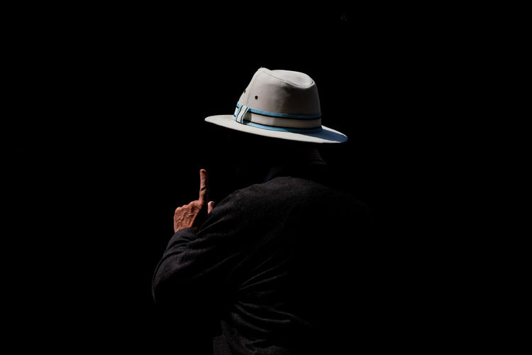 Rear view of person wearing hat against black background