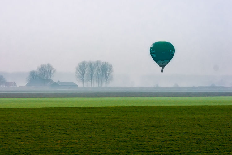 Saw a balloon landing in the fog. Distance is about 1KM, telelens (handheld; speed 1/200; F8) compressed everything. Original RAW very 'exposed to the right', Lightroom did a good job! Sony A700 EyeEm Market © Farmland The Netherlands Zeeuws Vlaanderen Balloon Distance Field Flying Fog Grass Hot Air Balloon Telelphoto Lens Zeeland