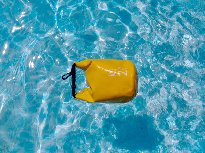 High angle  view of yellow dry bag floating in swimming pool