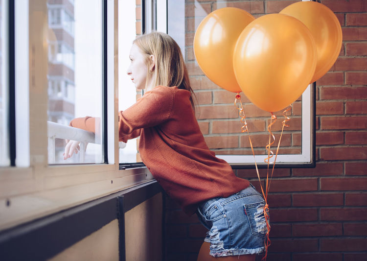 Side View Of Woman With Orange Balloons Looking Through Window While Standing At Home