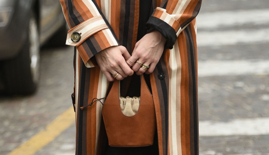 Midsection of woman holding purse while standing on road